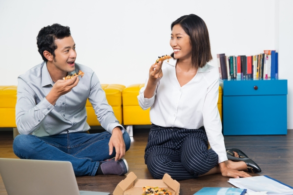 Asian couple eating pizza together