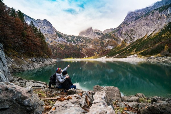 couple-by-a-lake-surrounded-by-mountains