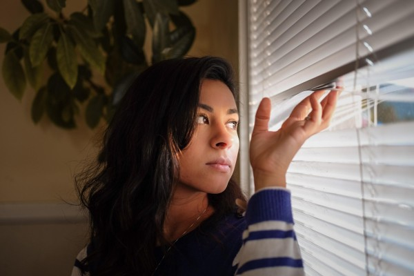 Woman looking outside through the window blinds.